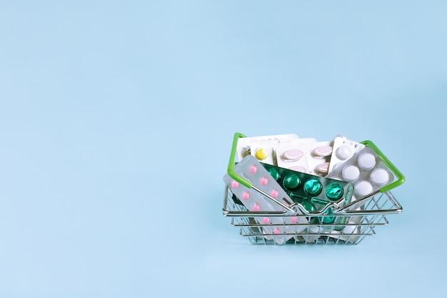 Bolle differenti della medicina nel canestro dell'acciaio inossidabile sul blu. medicina da vicino.