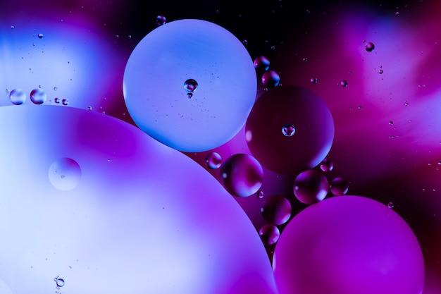Bolle e goccioline oleose del primo piano nel contesto acquoso variopinto