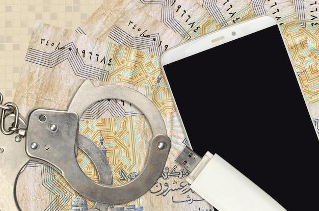 Bollette egiziane piastres e smartphone con manette della polizia