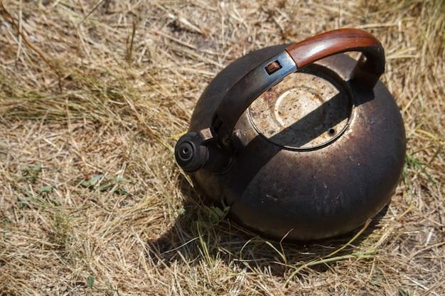 Bollitore del metallo affumicato primo piano che sta sull'erba asciutta vicino al falò
