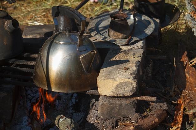 Bollitore del metallo affumicato primo piano su un forno casalingo sopra il fuoco e il cezva con caffè appena preparato