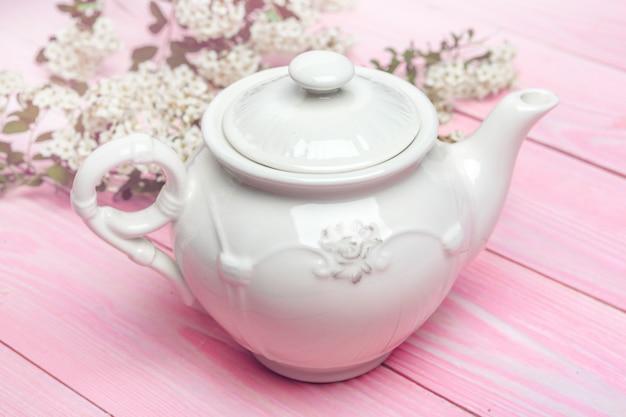 Bollitore di tè ceramico bianco sulla fine di legno della tavola su