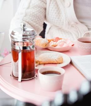 Bollitore per tè e biscotti di pasta frolla sul tavolo