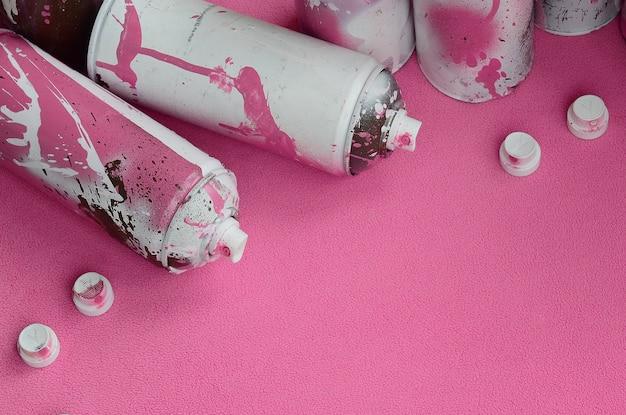 Bombole spray aerosol rosa e ugelli con gocce di vernice giace su una coperta