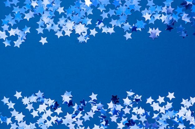 Bordo astratto blu della priorità bassa di natale, struttura della struttura con i coriandoli delle stelle su priorità bassa blu. spazio per il testo.
