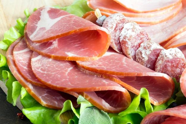 Bordo con prosciutto, pancetta, salame e salsicce su fondo di legno. taglio freddo.