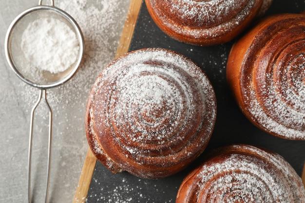 Bordo con rotoli di cannella con zucchero a velo sul tavolo grigio