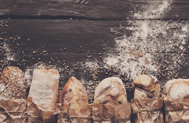 Bordo del pane su fondo di legno scuro. composizione di natura morta di pani interi marroni e bianchi con farina di frumento cosparsa intorno. concetto di panetteria, cucina e drogheria.