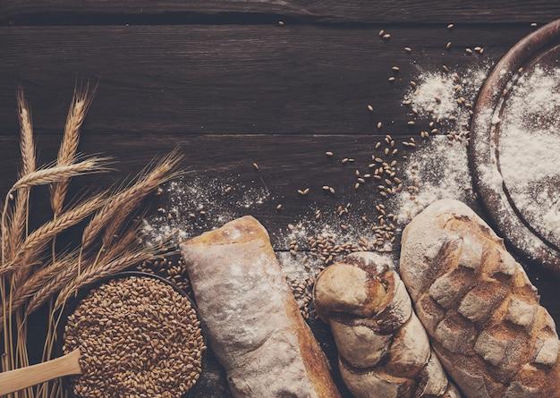 Bordo del pane su fondo in legno. pani interi marrone e bianco composizione di natura morta con spighe di grano sparse intorno. concetto di negozio di alimentari di panetteria e drogheria.