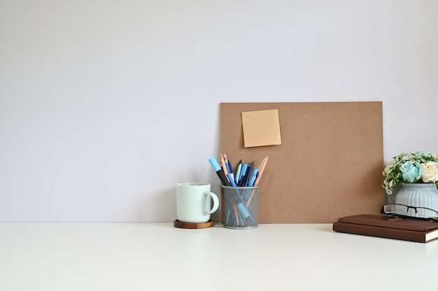 Bordo dell'area di lavoro dell'ufficio e nota appiccicosa, caffè con gli articoli per ufficio sullo spazio della copia della tavola.