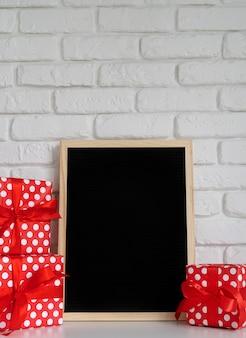 Bordo della lettera del feltro nero con i contenitori di regalo rossi sul muro di mattoni bianco