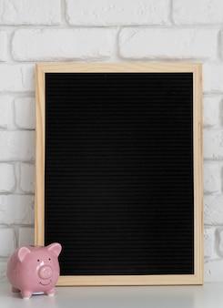 Bordo della lettera del feltro nero con il piccolo porcellino salvadanaio sul muro di mattoni bianco