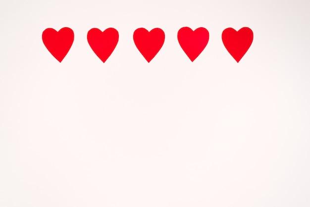 Bordo di cuori di carta rossa su sfondo bianco. biglietto d'auguri con copia spazio per san valentino