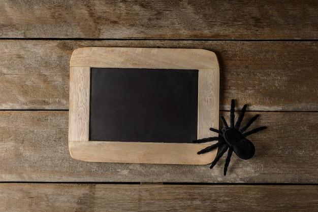 Bordo di gesso di halloween e ragno nero del giocattolo