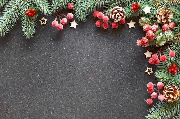 Bordo di natale decorato con ramoscelli di abete, bacche e pigne glassate su spazio scuro, testo
