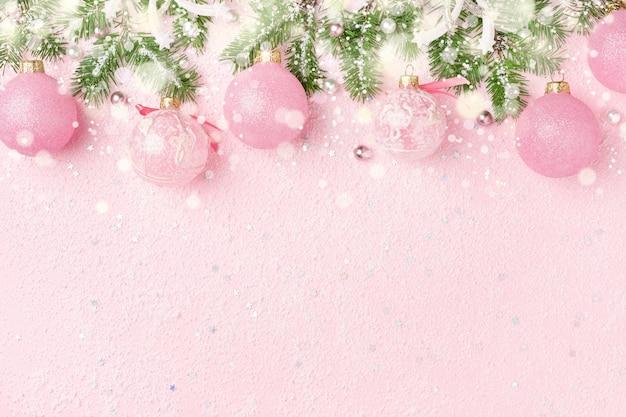 Bordo di natale degli ornamenti di nuovo anno, dell'abete verde e della neve sul colore rosa