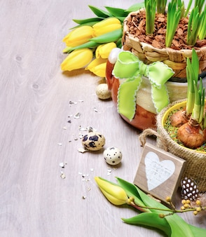 Bordo di pasqua con tulipani gialli e decorazioni naturali su legno