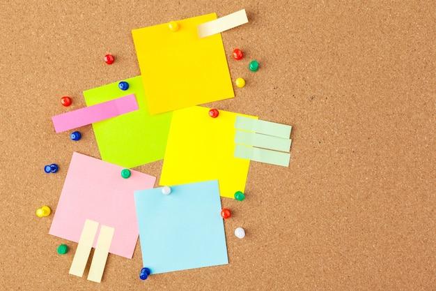 Bordo di sughero con diverse note vuote colorate con perni