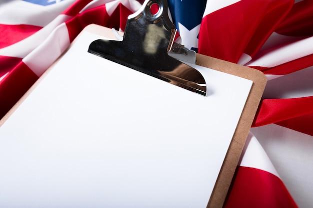 Bordo in bianco della clip e bandiera di usa su fondo di legno