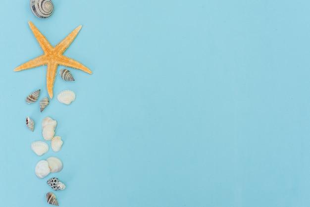 Bordo laterale di estate di sabbia, conchiglie e stelle marine su fondo di legno blu