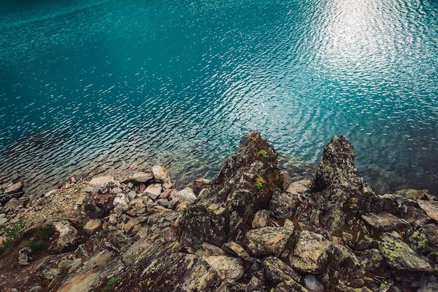 Bordo pietroso dell'acqua del lago azzurro della montagna