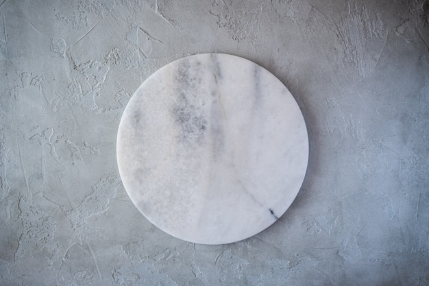 Bordo rotondo di struttura di marmo vuota bianca su fondo grigio. vista dall'alto. copia spazio.