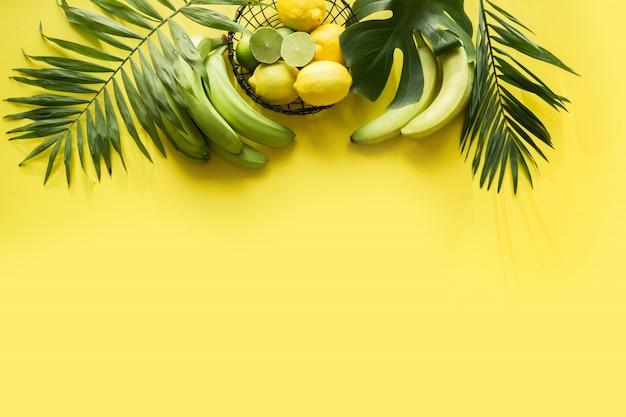 Bordo tropicale di frutta, banana, lime, foglie di palme su sfondo giallo incisivo. detox tour.