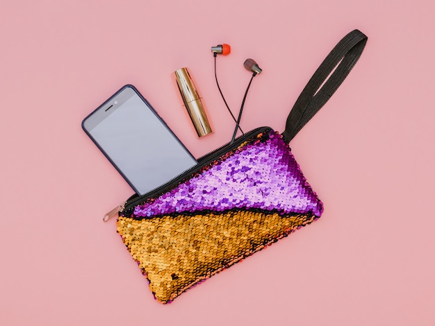 Borsa a due colori con auricolari, telefono e rossetto sul tavolo rosa