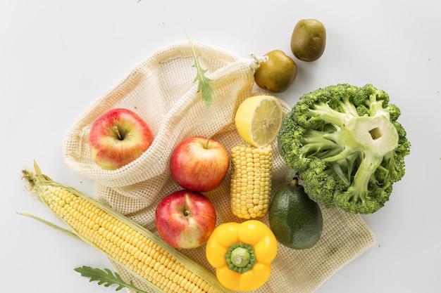 Borsa a maglie piene delle verdure e della frutta differenti dell'alimento salutare sulla vista superiore bianca