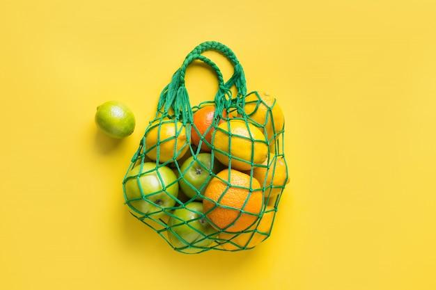 Borsa a rete con frutti su giallo.