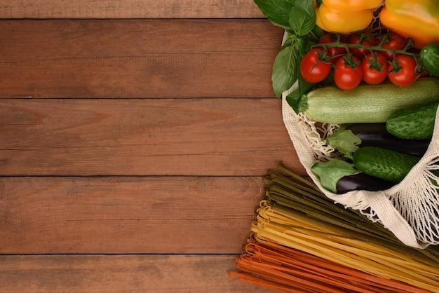 Borsa a rete con verdure e spaghetti vegetali su fondo in legno con copia spazio. zero sprechi. eco bag con pasta e verdure fresche.