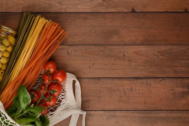 Borsa a rete con verdure spaghetti, pomodoro, basilico e olive. la pasta vegetariana ha messo nella borsa di eco su fondo di legno con lo spazio della copia.