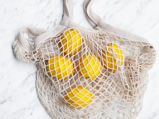 Borsa a rete in cotone vista dall'alto con limoni