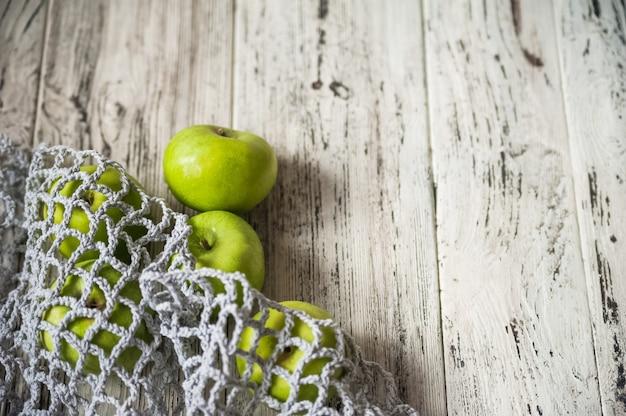 Borsa a rete piena di mele colorate dal giardino, su sfondo di legno grigio.
