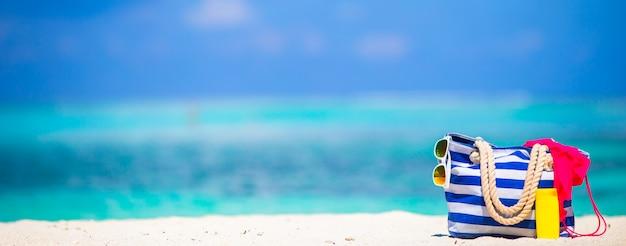 Borsa a strisce, asciugamano blu, occhiali da sole, bottiglia di crema solare e costume da bagno sulla spiaggia bianca
