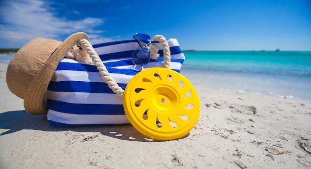 Borsa a strisce, cappello di paglia, crema solare e frisbee sulla spiaggia tropicale di sabbia bianca