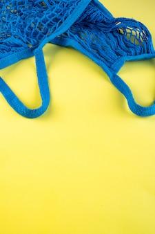 Borsa a tracolla blu realizzata in materiale ecologico su uno sfondo giallo brillante.