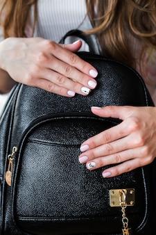 Borsa alla moda della giovane donna alla moda e manicure rosa