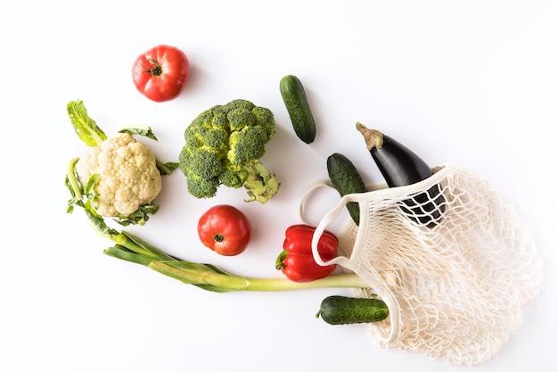 Borsa amichevole di eco di acquisto del cotone della tela con le verdure organiche sopra fondo bianco