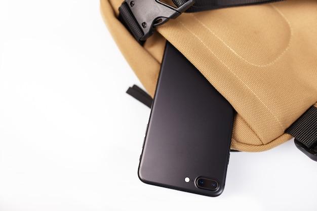 Borsa beige su un fondo isolato bianco con una tasca nascosta per un alto vicino del telefono cellulare
