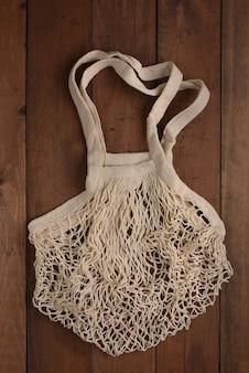 Borsa bianca della maglia di cotone su fondo di legno. concetto di rifiuti zero. vista dall'alto della shopping bag riutilizzabile. ecologia sicura.