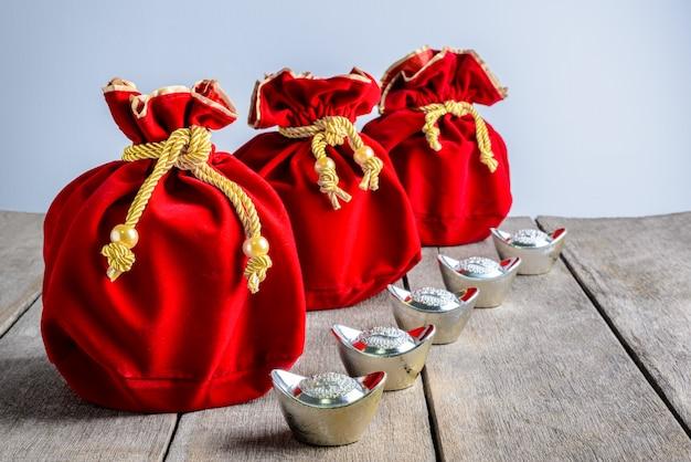 Borsa cinese in tessuto rosso di capodanno, e pow con denaro cinese fortunato e lingotto d'oro a forma di scarpa