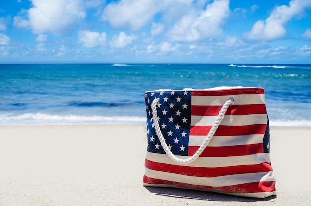 Borsa con i colori della bandiera americana vicino oceano sulla spiaggia di sabbia