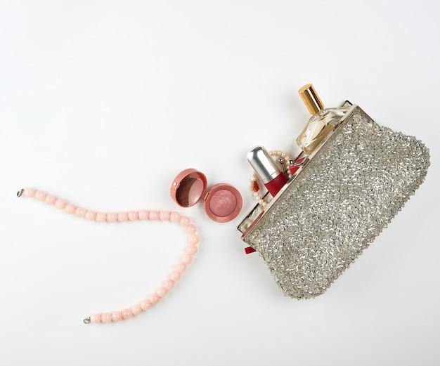 Borsa cosmetica aperta in argento e cosmetici e profumi per donna, rossetto rosso, profumo