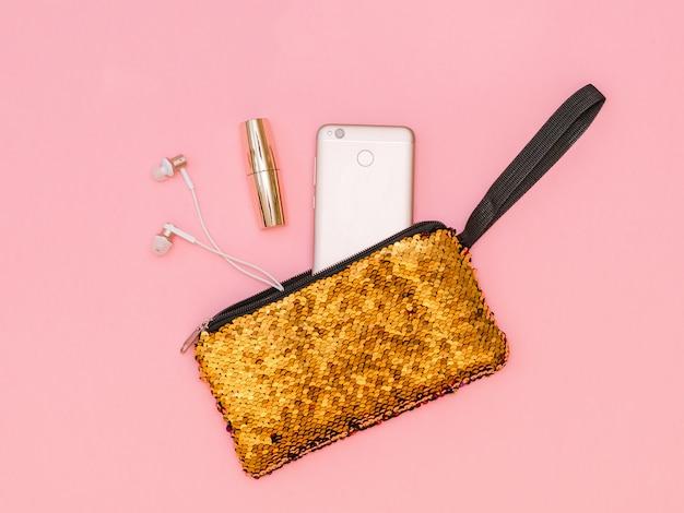 Borsa da donna dorata con telefono e rossetto su un tavolo rosa