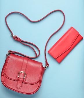 Borsa da donna in pelle rossa e borsa su sfondo blu pastello, accessori da donna, vista dall'alto, minimalismo