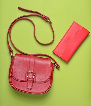 Borsa da donna in pelle rossa e borsa su sfondo verde pastello, accessori da donna, vista dall'alto, minimalismo