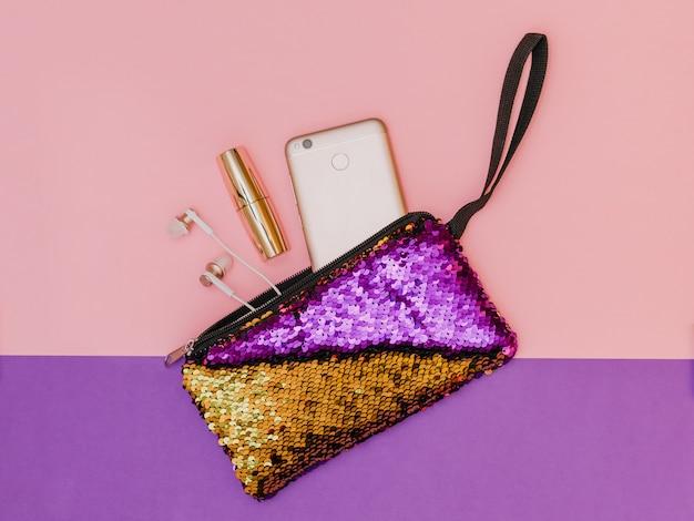 Borsa da donna viola con oro con telefono e rossetto su un tavolo bicolore