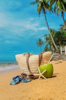 Borsa da spiaggia e cocco in mare.