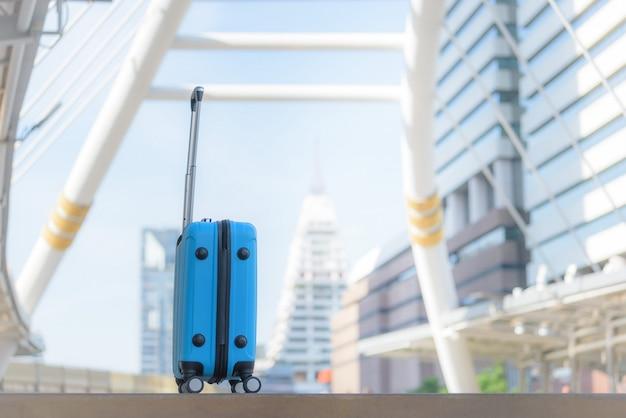Borsa da viaggio blu sul passaggio pedonale con sfondo sfocato città.